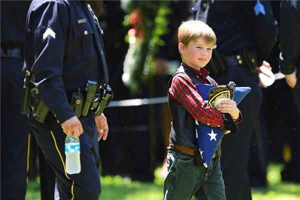 Magnus Ahrens mang một lá cờ Mỹ đã được xếp ngay ngắnsau lễ an táng cho cha của mình, là1 trong 5 cảnh sát bị bắn chết tại một cuộc biểu tình ở Texas gần đây.(Ảnh: Cooper Neill)