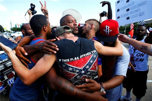 Một nhóm đàn ông bao gồmmột ngườimặc áo mang hìnhlá cờ liên minh, ôm nhau sau khi tham gia một vòng tròn cầu nguyện cho cuộc biểu tình The Blacks Lives Matter sau vụ nổ súng tại Dallas, Texas.(Ảnh: Carlo Allegri)