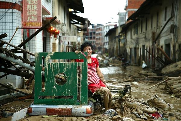 Một phụ nữ ngồi trong đống đổ nát của khu phố của cô sau khi cơn bão tràn qua Nepartak quận Minqing ở tỉnh Phúc Kiến, Trung Quốc.(Ảnh: China Stringer Network)