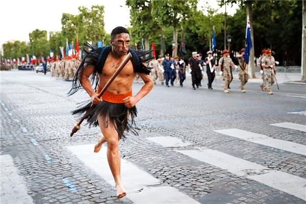 Một người lính Maori chạy ngang qua binh lính của New Zealand khi đangtiến quân xuống đại lộ Champs-Élysées ở Paris, trong suốtbuổi diễn tập của quân đội diễu hành ngày Quốc khánhhàng năm.(Ảnh: Thomas Samson)