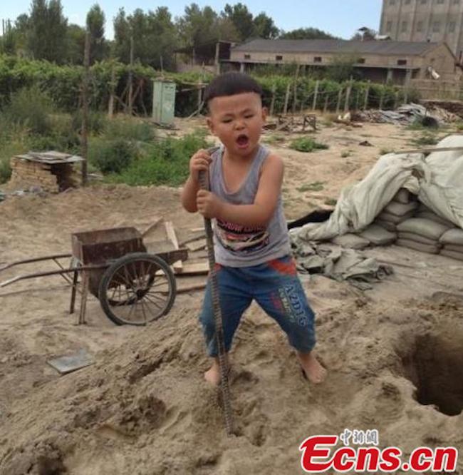Cậu bé mặc áo ba lỗ, quần bò lửng đứng trên đống cát, tay cầm thanh sắt và hát rất nhập tâm.
