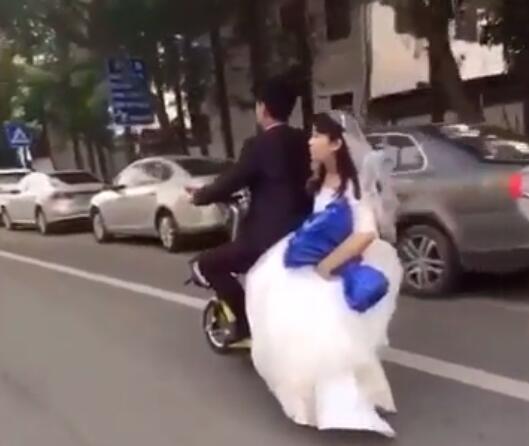 Đôi vợ chồng trẻ trông rất dễ thương,tình tứ khi mặc lễ phục cưới và đưa nhau về dinhbằng xe đạp điện.