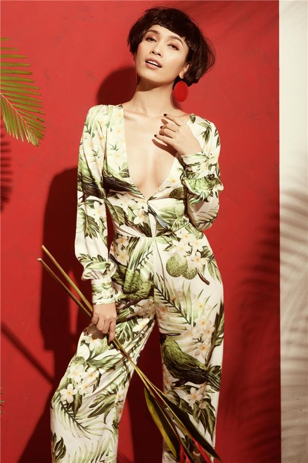 Ái Phương khoe khéo vòng 1 khiêm tốn trong thiết kế jumpsuit xẻ ngực sâu hun hút. Bộ trang phục lấy họa tiết hoa lá với sắc xanh, vàng pha trắng làm chủ đạo mang đến những dư vị ngọt ngào, mát mẻ trong mùa hè của những vùng đất miền nhiệt đới ấm áp.