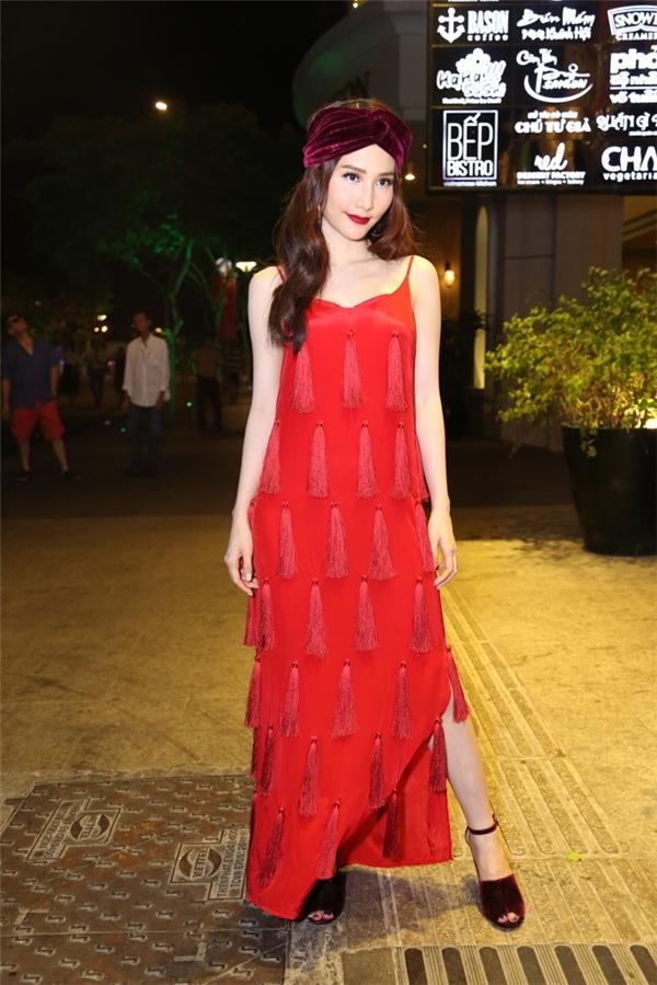 Diễm My 9x phối khăn màu trầm với váy suông rộng màu đỏ nổi bật.