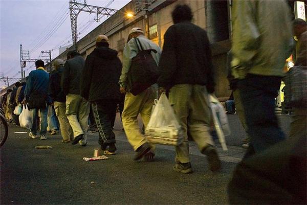 Đúng 5 giờ sáng, người dân Nishinari xếp hàng ngay ngắn đi vào trung tâm cứu trợ để nhận thức ăn và chỗ trú ban đêm.