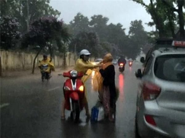 Cách đây không lâu, trong một ngày Hà Nội mưa tầm tã, hình ảnh cô gái đi xe máy dừng lại giữa đường, cởi áo mưa và mặc cho một bà cụ xa lạ đã khiến dân mạng vô cùng cảm phục.(Ảnh: Internet)