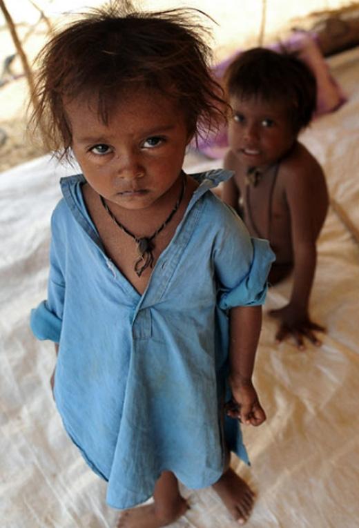 Đứa trẻ mới biếtđi chập chững đang đứng trong 1 chiếc lều tại trại tạm thời dành cho nạn nhân lũ lụt.