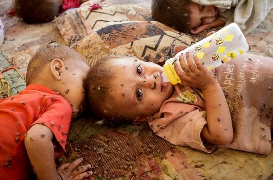 Những đứa trẻ Pakistan được cứu khỏi lũ lụtbị ruồi nhặng bao quanh đang nằm trên một con đường ởNowshera gầnPeshawar.
