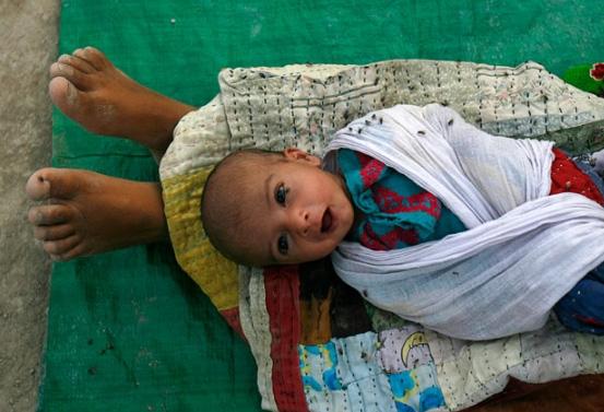 Shadab - 1 tuổi, nằm trên chân mẹ trong chuyếndi cư cùng gia đình đến trại cứu trợ vì lũ lụt ởSukkur.