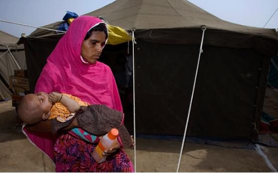 Người phụ nữ đang bế đứacon gái bị ốmAfsana Din rời khỏi trại ytế cứu trợ lũ lụt.