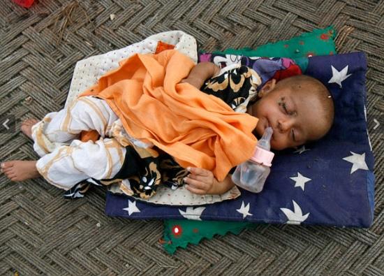 Nandni, 11 tháng tuổi đang ngủ trong khi mẹ cô bé đi chuẩn bị bữa tối tạitrại cứu trợ lũ lụt quân đội Pakistan.