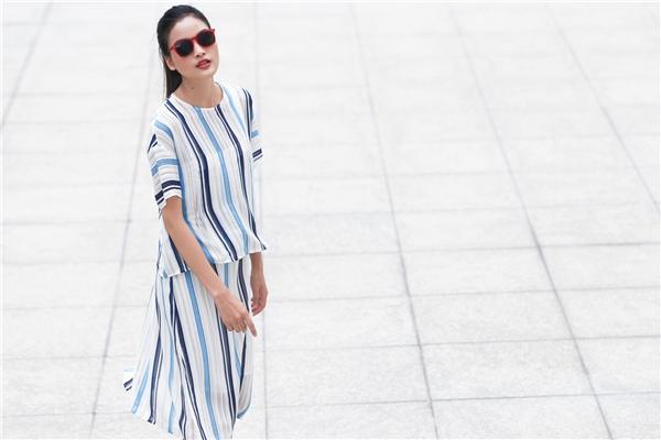 Chân váy xẻ tà mang diện mạo mới mẻ hơn khi được kết hợp cùng áo phom rộng cổ điển. Thiết kế tạo nên sự đồng điệu bởi chất liệu nhẹ nhàng, mỏng manh với 4 gam màu xen kẻ nhau gồm: xanh thiên thanh, xanh thẫm, trắng và be nhạt.