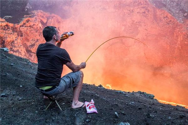 """Nhàmạo hiểm người New Zealand,Simon Turner có lẽ là người điên rồ nhất trong số những """"liều lĩnh gia"""" này. Anh đang ngồi trên một miệng núi lửa, uống bia, nhấm nháp mấy viên kẹo và câu cá."""