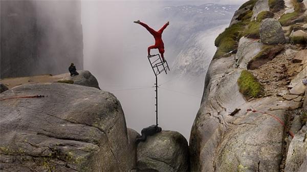 Nghệ sĩ ngườiNa Uy Eskil Ronningsbakken đang giữ thăng bằng trên một chiếc ghế ở vách đá cao khoảng 1000m.