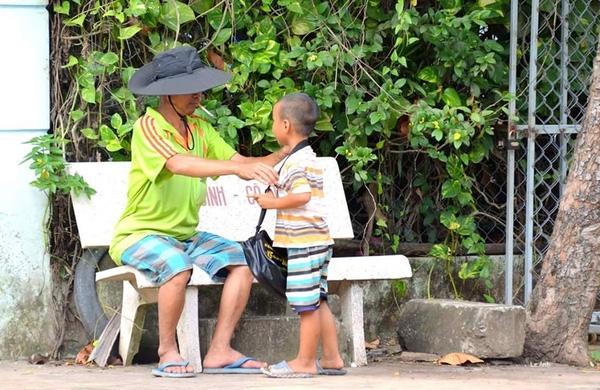Đếm lại tập vé số xong, người cha đeo chiếc túi cho con trai nhỏ và trò chuyện với cậu bé.