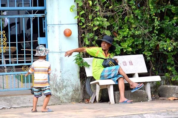 Người cha già nua dù khá mệt mỏi nhưng vẫn mỉm cười nhìn con trai nô đùa với trái bóng.