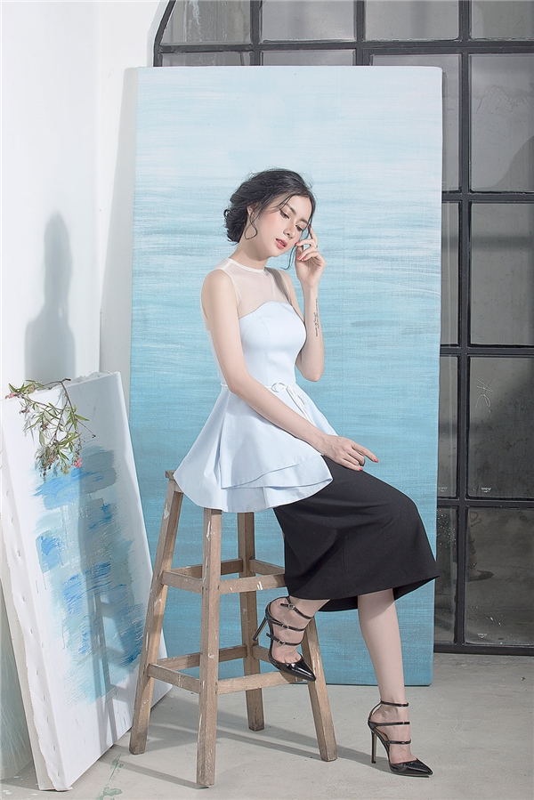 Áo peplum với tông màu xanh lơ được chọn phối với chân váy rộng mang lại vẻ đẹp cổ điển, thanh lịch. Thay vào chân váy, quần âu ống suông cũng là một sự kết hợp tuyệt vời với dáng áo này.