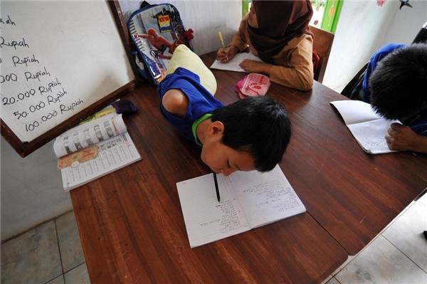 Hình ảnh Tiyo (11 tuổi) cố gắng viết chữ bằng miệng.(Ảnh Barcroft Media)
