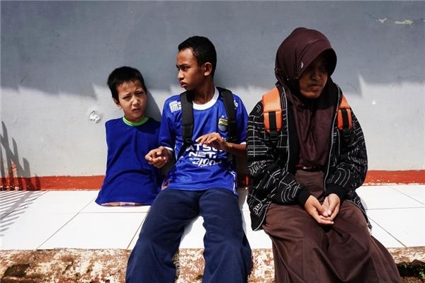 Hình ảnh Tiyo đang ngồi nói chuyện, chơi đùa cùng bạn bè trong trường.(Ảnh Barcroft Media)