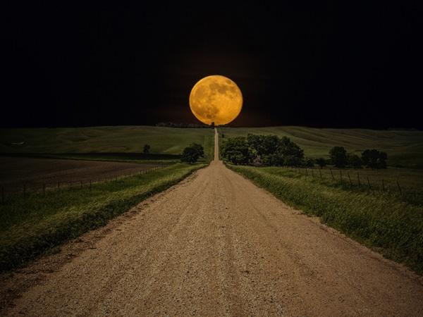 """Khoảnh khắc mặt trăng """"hạ"""" sátđường chân trời trên một con đường quê ở Nam Dakota, Mỹ."""