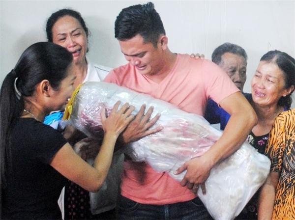 Người thân của thầy Tiên khóc nức nở khi ôm thi thể một trong hai bé chết cháy. (Ảnh: Nhật Tân)