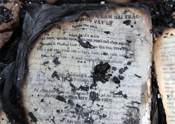 Trong nhà thầy Tiên có nhiều vật dụng dễ cháy. Trong ảnh là sách và tài liệu môn Vật lý còn sót lại nhưng cũng bị cháy xém. (Ảnh: Việt Tường)