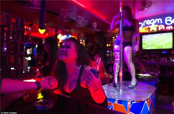 Một cô gái bar đang lả lơi tiếp chuyện khách trong khi đằng sau làmột đồng nghiệp đang biểu diễn múa cột.