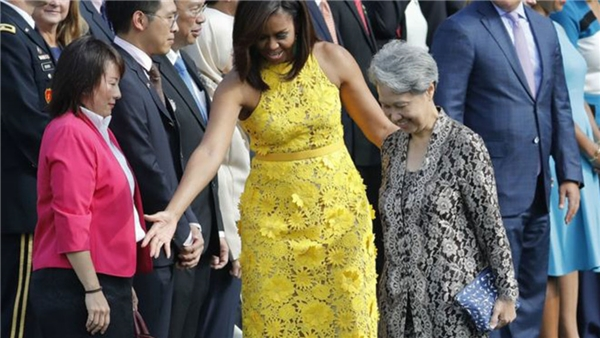 Bà Hà Tinh cầm cái bóp trị giá 11 USD khi gặp phu nhân tổng thống Mỹ Michelle Obama tại Nhà Trắng. (Ảnh: AP)