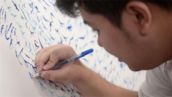 Chàng trai tự kỉSee Toh Sheng Jie vẽ hình khủng long. (Ảnh: STRAITS TIMES)