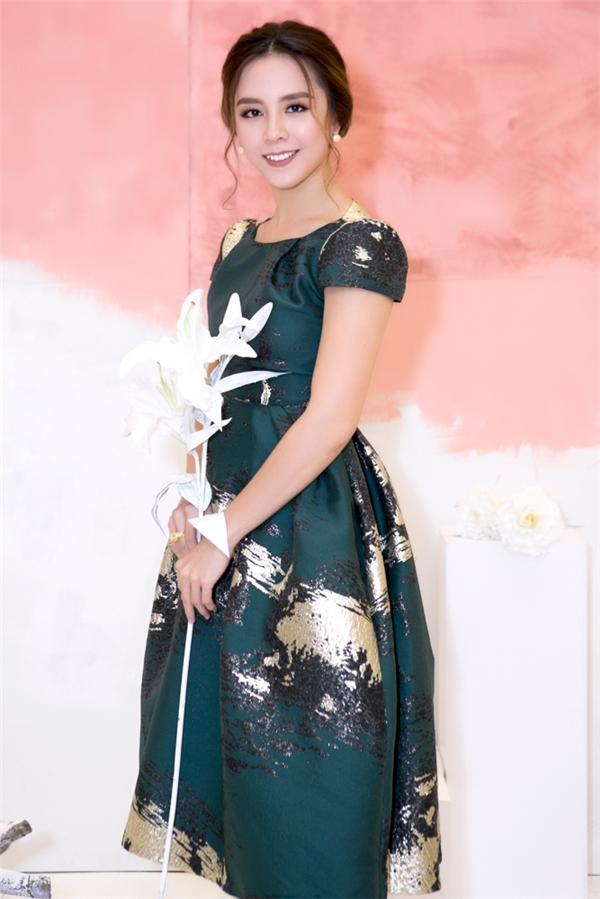 Á hậu Hoàn vũ Việt Nam 2008 Dương Trương Thiên Lý diện váy xanh trầm mặc kết hợp họa tiết màu vàng ánh kim nổi bật.