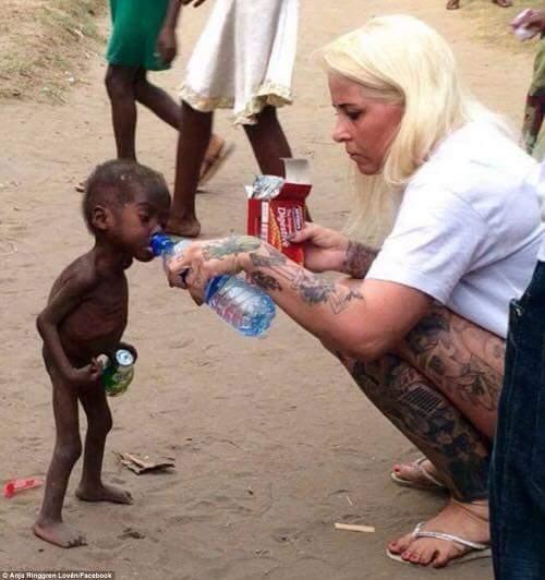 Khoảnh khắc nhói lòng khi một nữ tình nguyện viên cho em bé 2 tuổi ở Nigeria. Cậu bé này bị xa lánh, hắt hủi thậm chí bỏ đói vì nghi ngờ là phù thủy.(Ảnh: Internet)