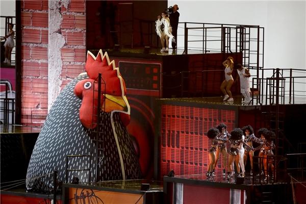 """Khán giả có dịp bất ngờ khi một chú gà trống khổng lồ đột nhiên từ đâu chui lên, xuất hiện trên sân khấu. Chính sự có mặt của """"nhân vật lạ"""" này đã góp phần lí thú cho màn biểu diễn cũng như tạo được sức hút mãnh liệt đếnđông đảo những người chứng kiến."""