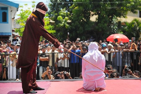 Một người thực thi tôn giáo đang quất roi vào một thanh niên Acehnhư sự trừng phạt cho việc hẹn hò ngoài hôn nhân, trái với pháp luật Sharia bên ngoài thánh đườngở Banda Aceh, Indonesia. NgườiAceh ngày càng trở nênbảo thủ hơntrong những năm gần đây và là dân tộcduy nhất ở Indonesia còn áp dụngluật Sharia.
