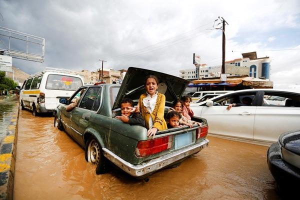 Trẻ em ngồi trong cốp xe trên đường phố bị ngập lụt ở Sanaa, Yemen.