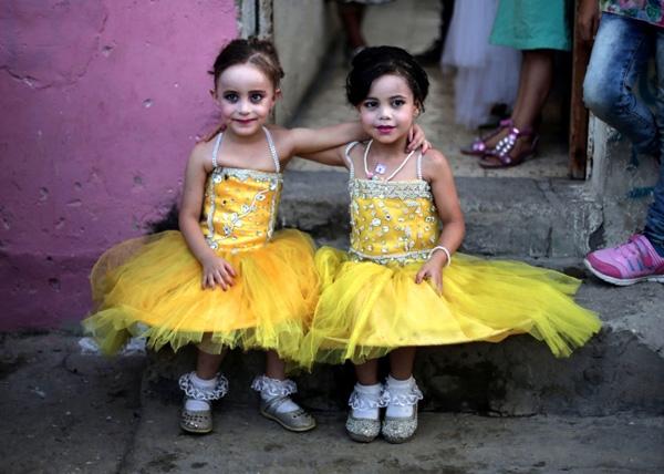 Hai bé gái đang chụpảnh trong buổi tiệc cưới của mộtchú rể Palestine ở thành phốGaza.Đám cưới như một niềm vui ngắn ngủi thoángqua những ngàybuồn rầu, ảm đạmở Dải Gaza, một vùng lãnh thổ ven biển Palestine bịkiểm soát bởiquânHamas.Đối với cả người Gazanghèo khổ và khá giả, đám cưới là một điều gì đó rất xa hoa.