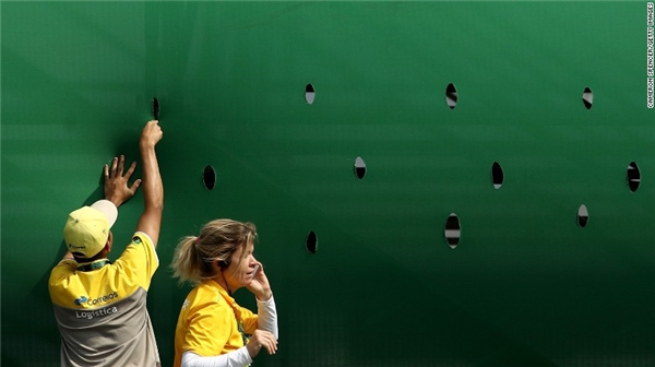 Một sốtình nguyện viên đang tiến hành cắt lỗ trên các bức màn xung quanh khu vực khán đài bởi vì những cơn gió mạnh thổi qua đã khiến cho một số trận đấu bị trì hoãn và hủy bỏ.