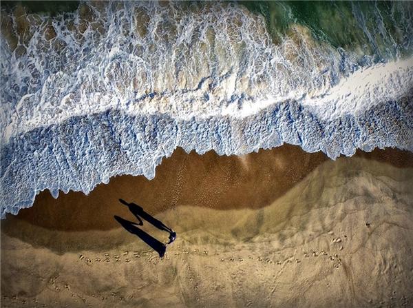8. Hình bóng của một cặp đôi in trên bãi biển tạo nên hình ảnh quá ấn tượng.