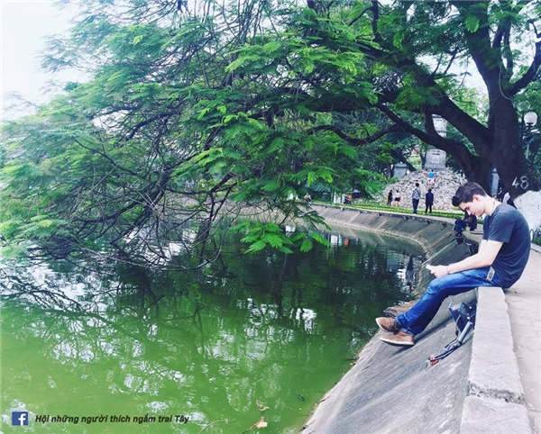 Anh Tây ngồi đọc sách bên Hồ Gươm vào một buổi sáng đẹp trời.