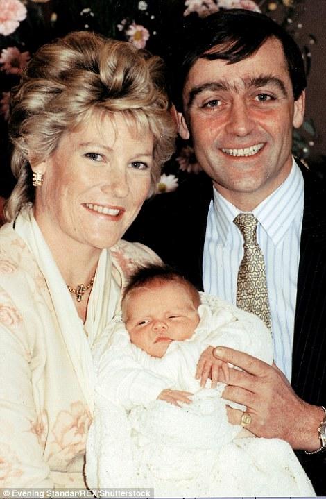 Hugh trong vòng tay nâng niu của bố mẹ.