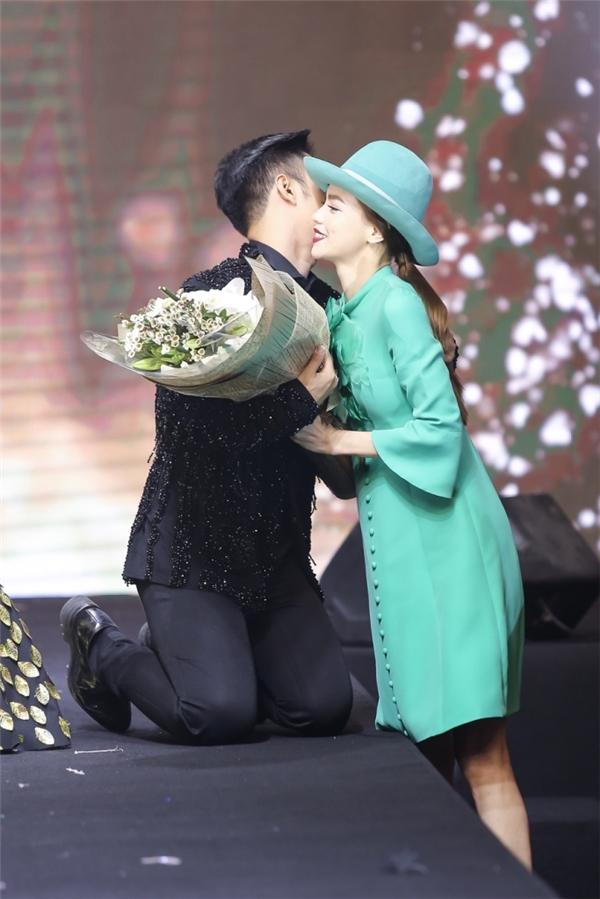Nữ ca sĩ diện bộ váy xanh ngọc và mũ đội đầu cùng tông theo phong cách thập niên cũ.