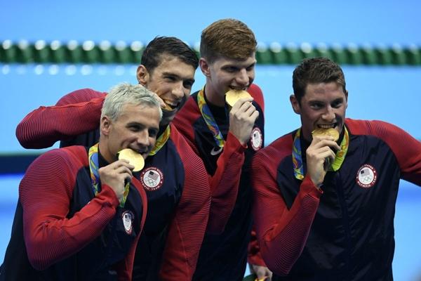 Michael Phelp chắc hẳn đang vô cùng mỏi răng khi liên tục phải cắn những tấm huy chương anh giành được.
