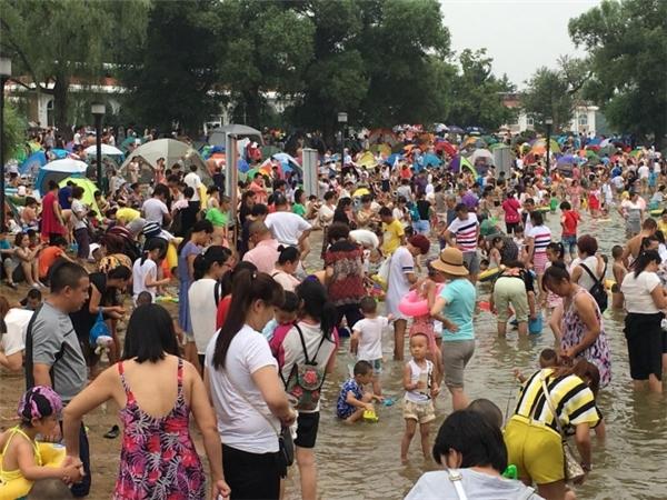 Hàng nghìn người dân thành phố Thường Xuân, tỉnh Cát Lâm dẫn con nhỏ đi tránh nóng.