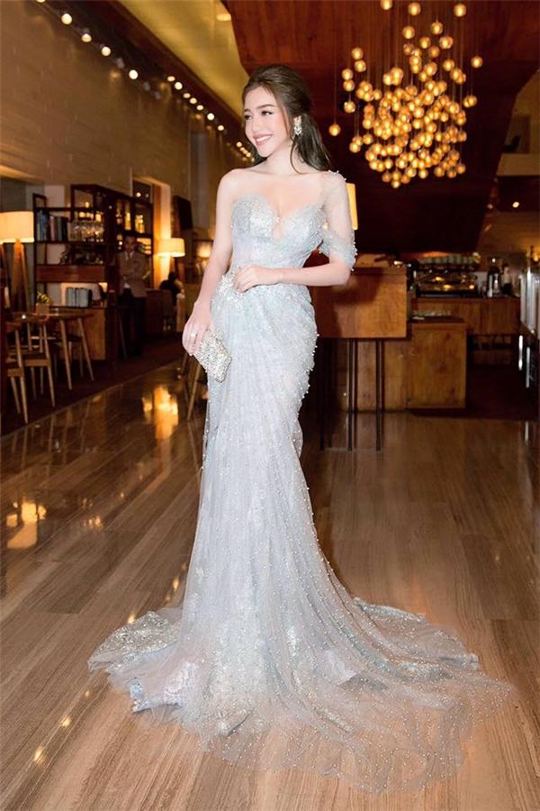 Váy đuôi cá cũng là lựa chọn của Elly Trần khi tham gia một đêm tiệc tuần qua. Dù thiết kế lấy tông màu xanh lơ làm chủ đạo nhưng vẫn đủ tạo ấn tượng bởi chất liệu ren, voan xuyên thấu mỏng tang. Nhà thiết kế Anh Thư khéo léo sử dụng ngọc trai tạo hiệu ứng bắt sáng cho bộ váy trông tựa như màn sương sớm long lanh, tuyệt diệu. (Điểm: 9)