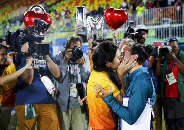 Isadora Cerullo, vận động viên bóng bầu dục người Brazil hôn côbạn gái Marjorie,một tình nguyện viên Olympic sau khi nhận lời cầu hôn bên lề buổi lễ trao huy chương bóng bầu dục nữ.