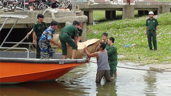 Lực lượng biên phòng và người dân cùng đưa thi thể cô gái xấu số lên bờ. (Ảnh: Nguyễn Tú)