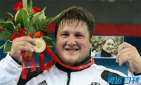 """Lực sỹ cử tạ Matthias Steiner khi giành Huy chương vàng ở hạng cân 105 kg tại Olympic Bắc Kinh 2008 đã dành tặng người vợ thân yêu của mình qua bức ảnh. Vợ của anh mất trước đó 1 năm vì tai nạn giao thông. """"Chiếc huy chương vàng này tôi dành riêng cho người vợ đầu tiên. Mặc dù trong suốt cuộc thi, tôi đã không nghĩ về vợ mình, nhưng cô ấy là động lực của tôi để chiến đấu"""", VĐV người Đức gốc Áo chia sẻ."""