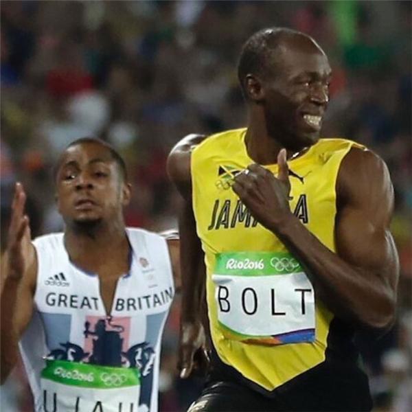 """Một VĐV khác thì đang chạy """"trối chết"""" trong khi Bolt nhởn nhơ cười làm duyên với cánh phóng viên."""