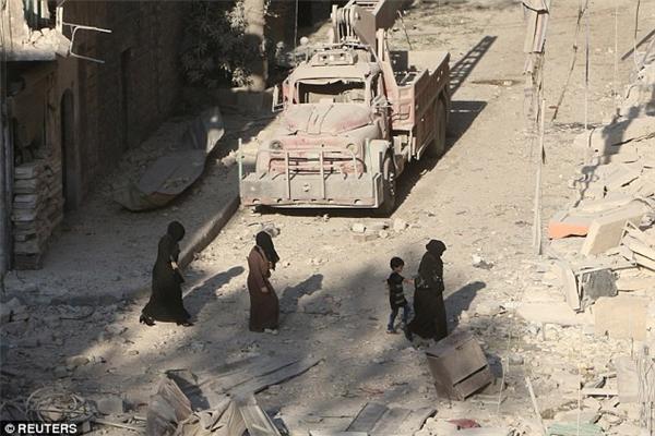 Phụ nữ và trẻ em len lỏi giữa đống đổ nát sau vụ không kích ở Aleppo.(Ảnh: Reuters)