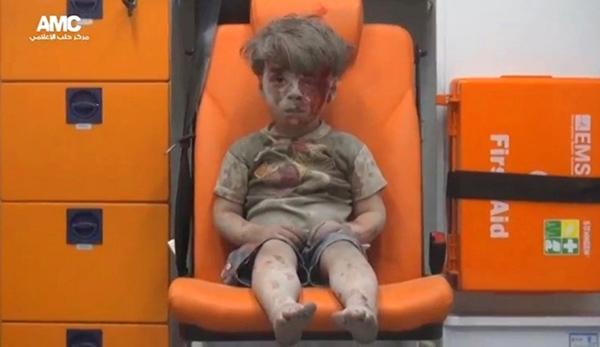 Hình ảnh cắt từ một video đang được cộng đồng thế giới quan tâm cho thấy một cậu bé người dính đầy bụi bẩn, ngồi bất động thất thần trên xe cứu thương saucuộc tấn công ởAleppo, Syria.