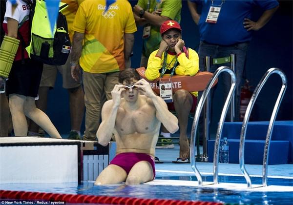 Một nhân viên cứu hộ với dáng vẻ ủ rũ và gương mặt buồn chán khi các VĐV bơi khởi động trước cuộc thi.